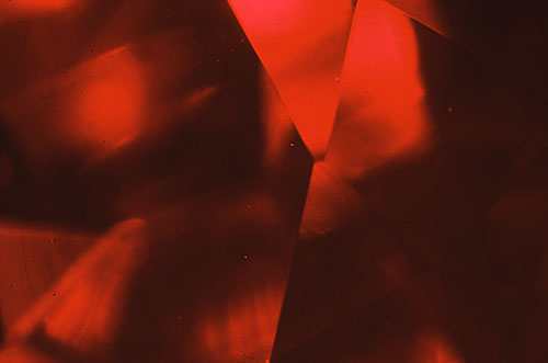 Figure 3. Using darkfield illumination this Kashan flux-grown synthetic ruby looks virtually flawless. Magnified 15×. Photomicrograph © John I. Koivula, microWorld of Gems.