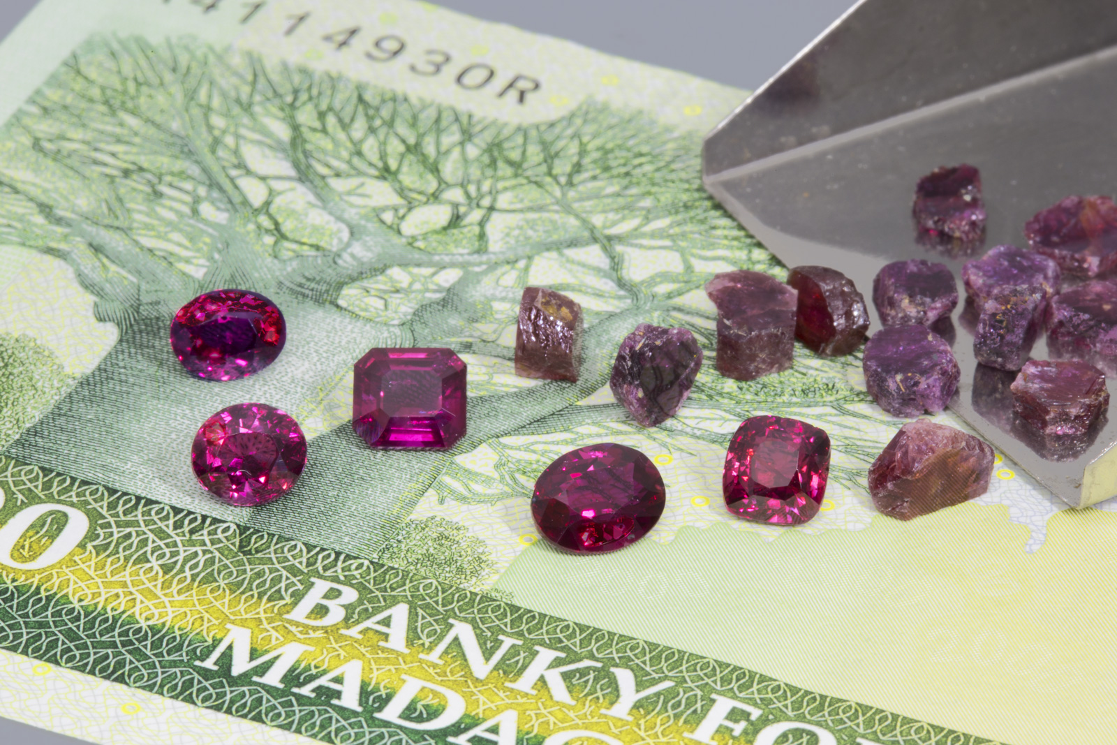 Faceted Madagasar rubies from the 2015 find, along with rough rubies from Moramanga collected by the author in 2005. The faceted stones are between 1.2 and 1.3 ct each. Photo: Wimon Manorotkul/Lotus Gemology.