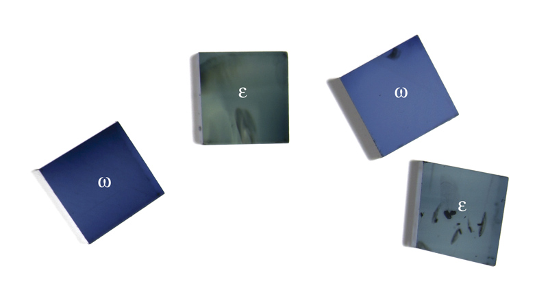 Figure 15. Small cubes of blue sapphire while viewed perpendicular to the optic axis through a polarizing filter. Rotating either the gems or polarizer will switch the two pleochroic colors of each piece. Photo: Wimon Manorotkul