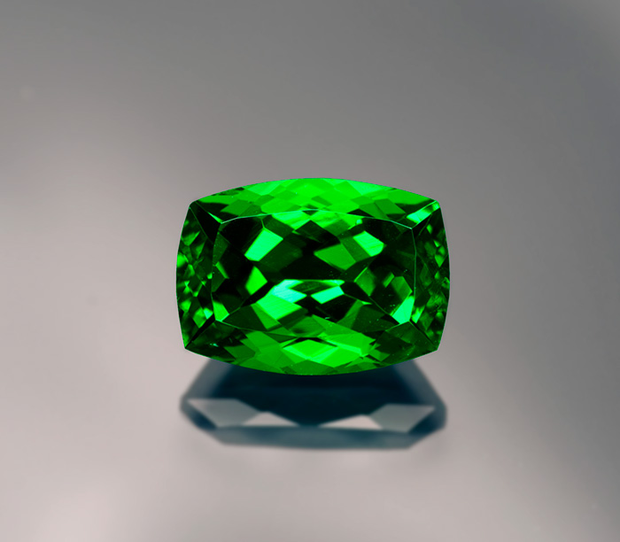 Figure 13. The color of this 7-ct tsavorite garnet is darker on the ends than in the center. This is not due to pleochroism—garnet is singly refractive—but an illustration of the Beer-Lambert law, where longer light paths result in greater absorption. Gem: Palagems.com; photo: Wimon Manorotkul