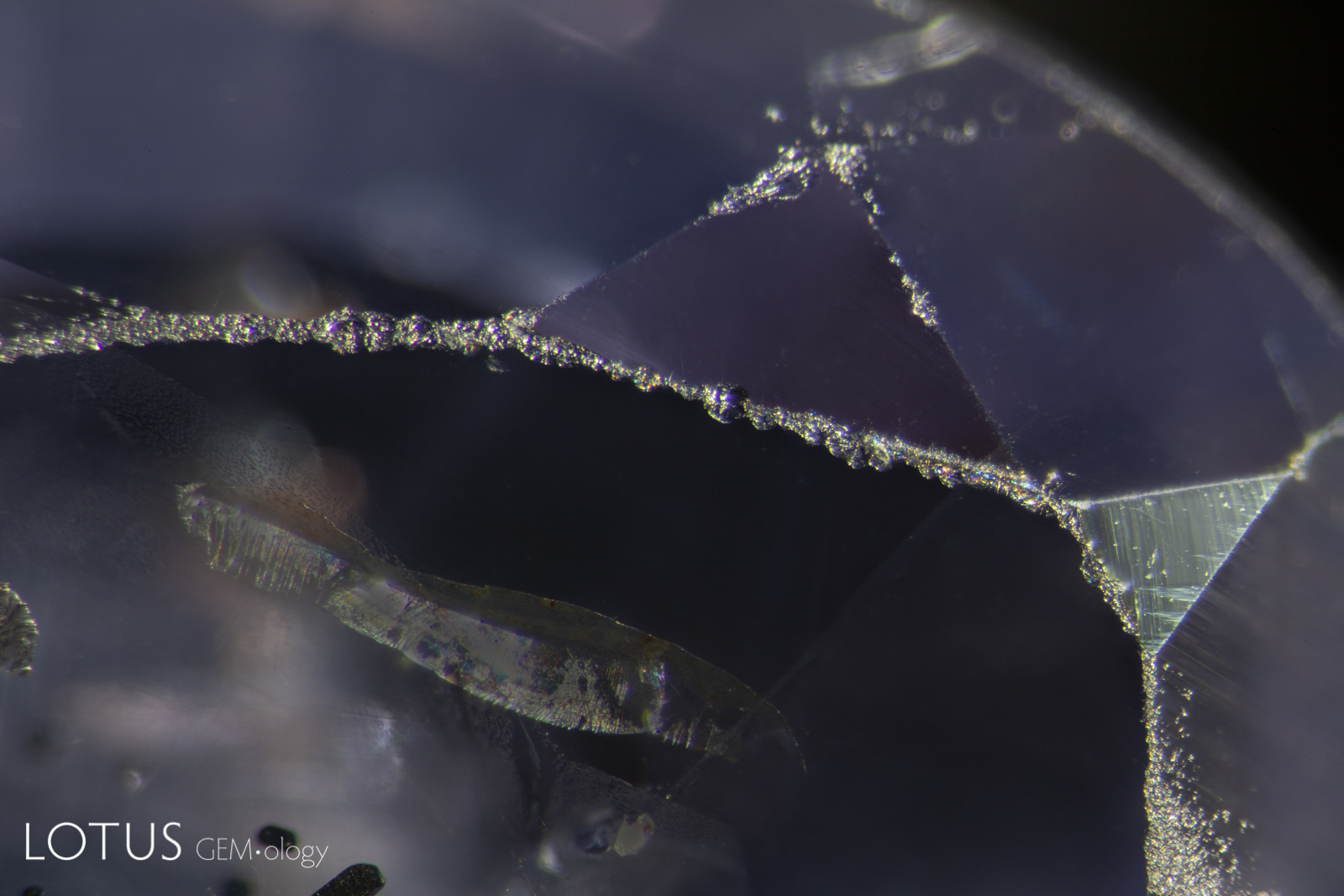 Untreated Ceylon sapphire showing wear marks with extensive facet abrasions and chips. This amply demonstrates that sapphire is somewhat brittle by nature.