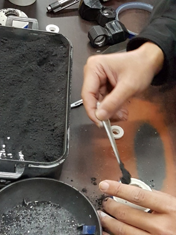 The sapphire to be treated is placed into a crucible (left). Generally only one stone per crucible is treated. The crucible is then packed tightly with graphite powder. The graphite not only produces a reducing atmosphere, but also ensures that the heat of the furnace is equally distributed.