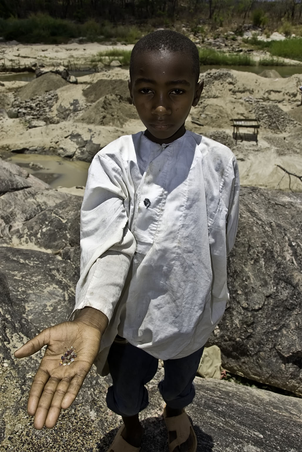 A young boy along the Muhuwesi River with a handful of gems.
