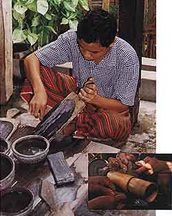 In Mandalay, cutters still use a board coated with a mixture of carborundum (of various grits) and hard wax to shape cabochons (photo by Mark Smith). They then polish jadeite on bamboo lathes, often without any abrasive