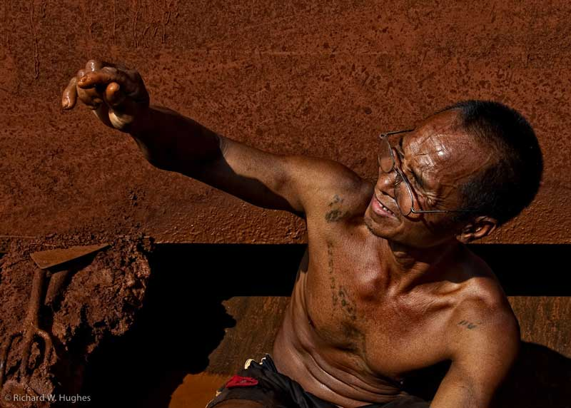 One of the last remaining sapphire miners at Khao Ploi Waen examines a find