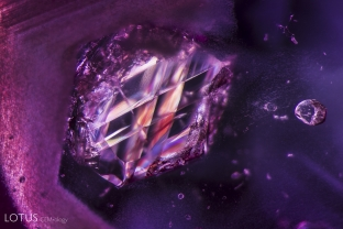 This calcite crystal inside a Burmese ruby shows polysynthetic twin planes.