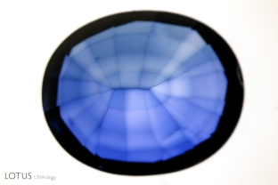 Color concentrations following facet edges of this titanium diffused synthetic sapphire become evident when it is immersed in diiodomethane. Studies have shown that this is more pronounced on synthetic seeds than on natural seeds, because the diffusion rate is slower in the synthetic (due to more Fe in the Ti-rich powder). In the synthetic, Fe must be added to the powder and this slows down the diffusion, where in the natural, the gem already contains enough Fe, and so pure Ti can be used.