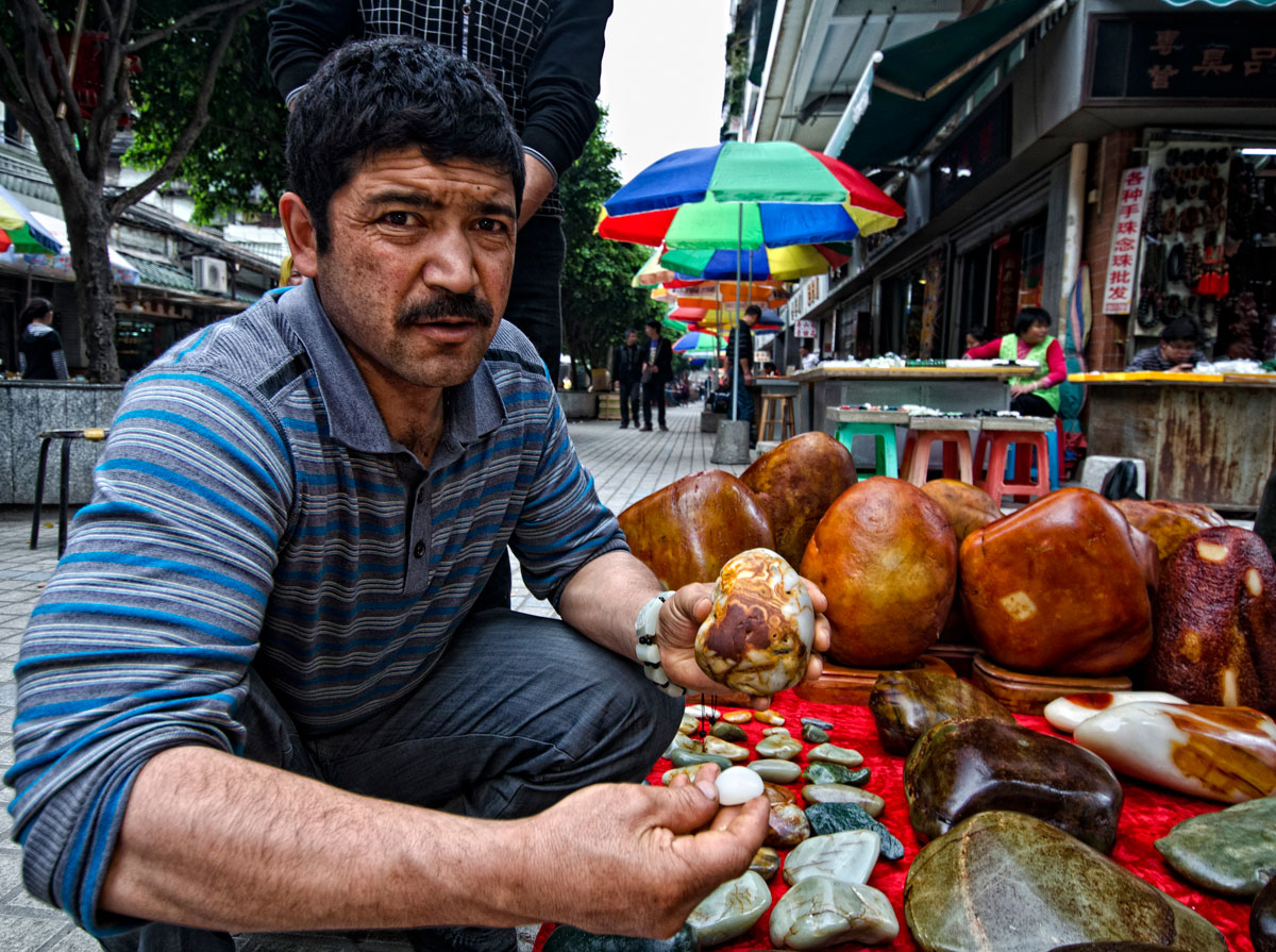 Figure 5. A Uighur man showing what looks like Chinese nephrite in Guangzhou's Hualin Street jade market. Photo: Richard W. Hughes.