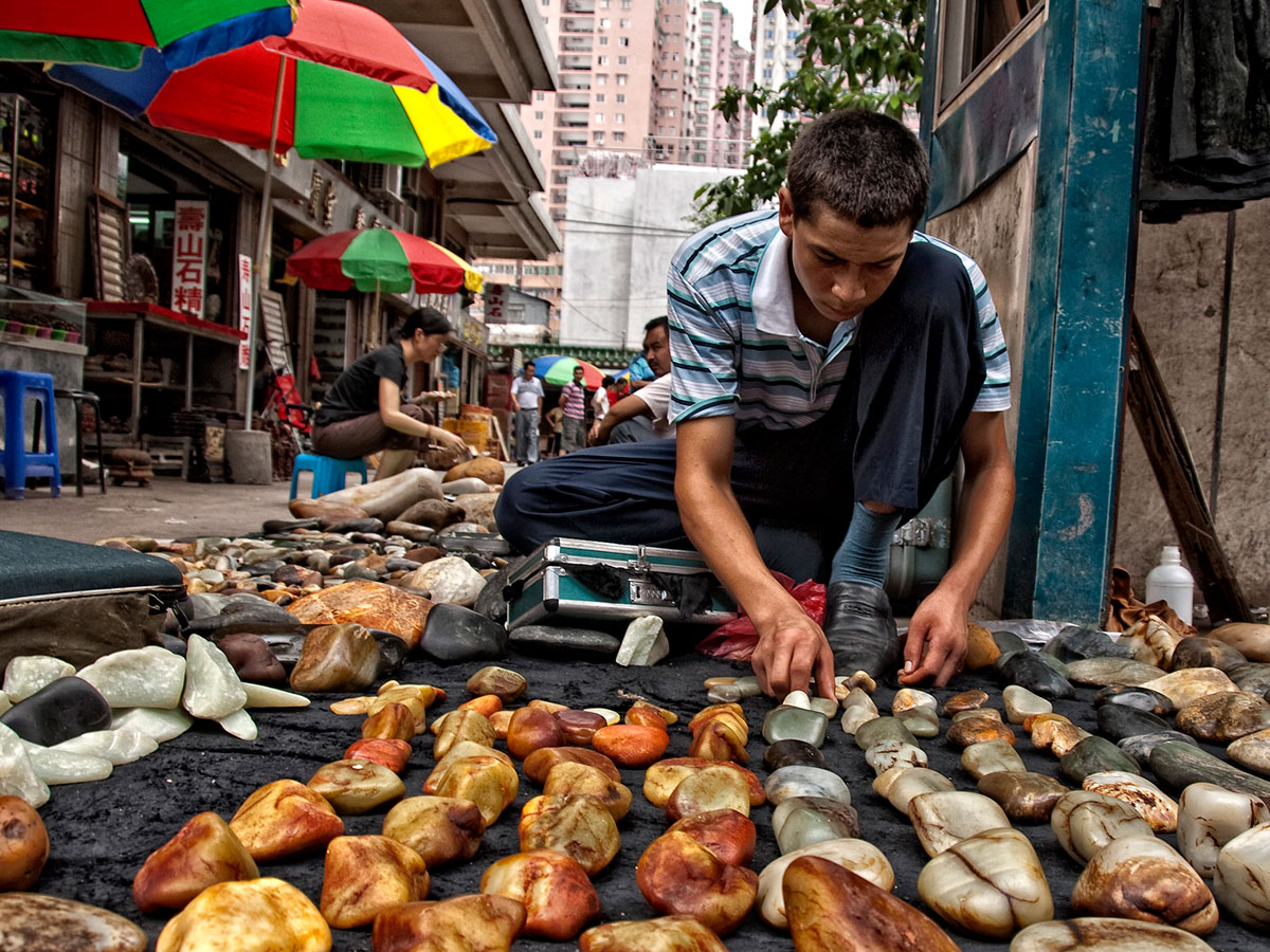 Figure 4. A Uighur man lays out his wares in Guangzhou's Hualin Street jade market. China's nephrite mines are located near Hotan (aka Khotan, Hetien), in western China's Xinjiang province. Photo: Richard W. Hughes.