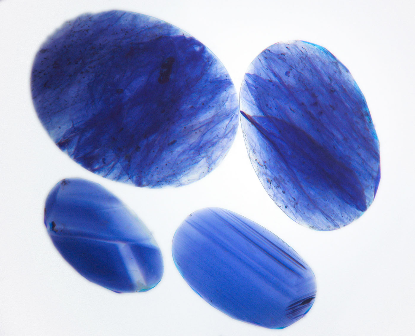Figure 12. Immersion in di-iodomethane (methylene iodide) in diffuse light-field illumination quickly reveals the blue color concentrations in the cobalt-glass filled sapphires (top two stones), whereas natural sapphires show angular color zoning (lower two stones). Image corrected to remove yellow color of liquid. Photo: Wimon Manorotkul