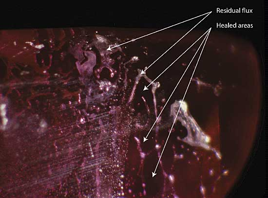 Figure 8. Residual flux Residual flux in a flux-healed fracture within a heat-treated Mong Hsu ruby. The areas (in the plane of the fracture) between the flux-filled channels consist of healed ruby. Photo: R.W. Hughes