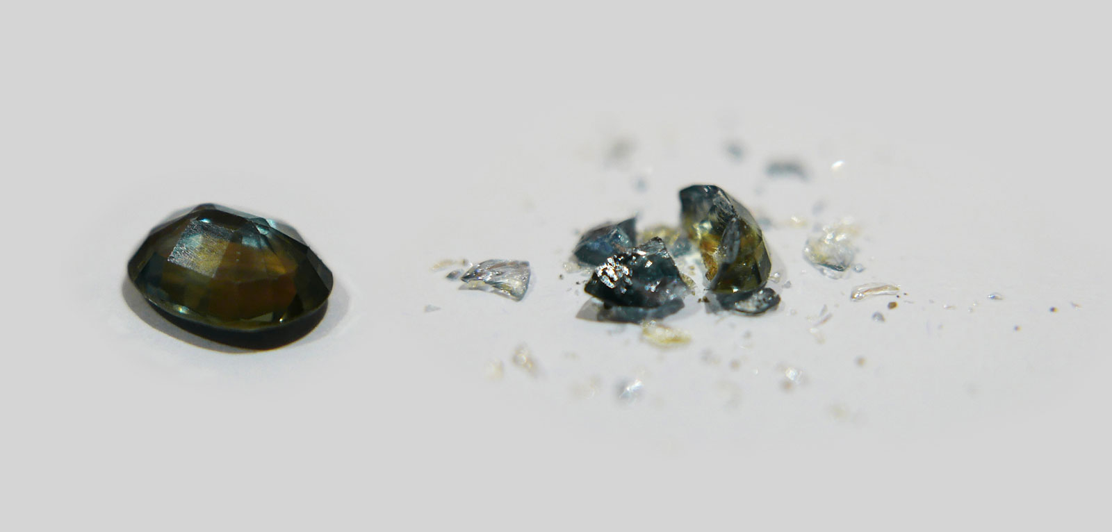 A basalt-related sapphire (left) that was heat treated by normal methods was subjected to a hammer test, which caused it to break into many fragments (right).