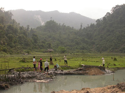 Spinel and ruby mining in rice fields near An Phu village, Luc Yen region, Vietnam. In the background are white marble cliff where spinels are also mined. Luc Yen Vietnam. Photo: V. Pardieu, 2005.