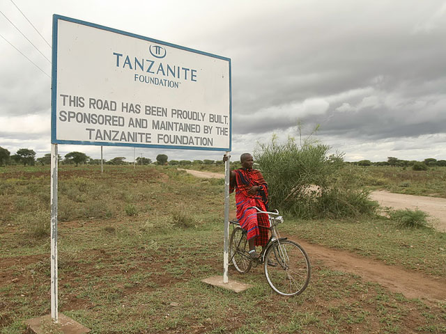 A Masai next to the sign and road to Merelani. Photo: Tanzanite Foundation