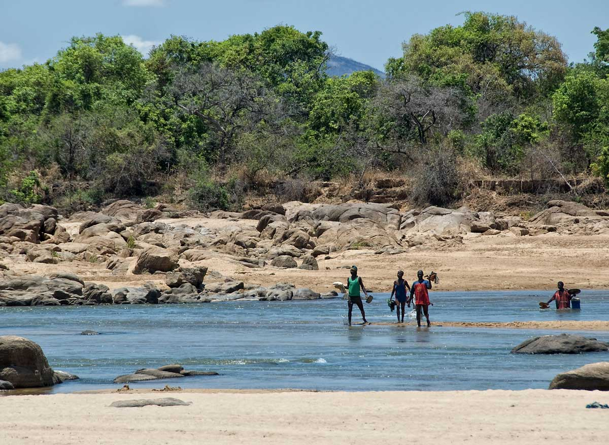 Miners fording the Ruvuma river that separates Tanzania (near bank) from Mozambique (far bank), in Tanzania's Tunduru district. Gems are found on both sides of the river. Photo: Richard W. Hughes