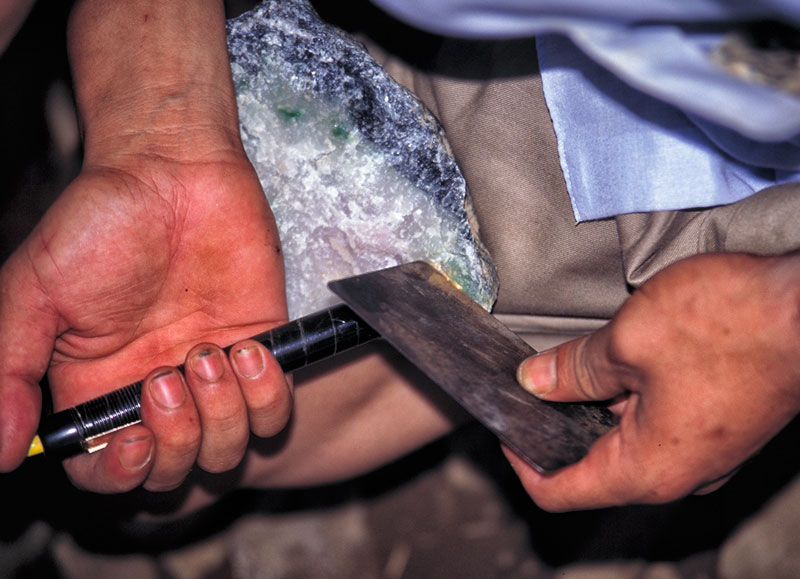 "Figure 20. The ""Golden Hand"" To get a better idea of the quality of color in this boulder, the dealer places a metal plate at the far side of a small area with potential and then uses a penlight to illuminate it. Photo © Richard W. Hughes."