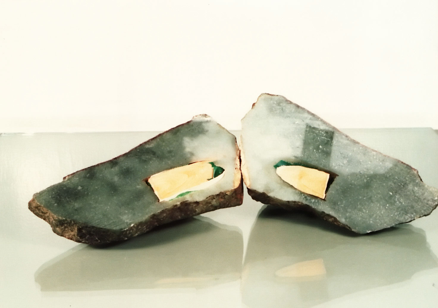 Figure 35. This jadeite boulder had a hole drilled in it from one side to just beneath the surface on the opposite side. A green glue was placed inside near the surface, with a wooden rod added. Then the drill hole was carefully concealed to hide the evidence. Thus when a strong light was shone onto the boulder's surface, a rich green color was revealed. Photos: Richard W. Hughes
