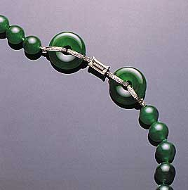 "Figure 23. This necklace, which contains a total of 65 beads (7.8–9.8 mm in diameter) and two matching hoops, illustrates the optimum ""vivid emerald green"" color in fine jadeite. Note also the very fine ""old mine"" texture and translucency. Photo courtesy of and © Christie's Hong Kong and Tino Hammid."