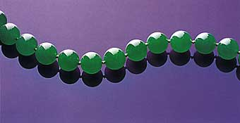 "Figure 25. Uniformity of a fine ""emerald"" green color, superb translucency, size, and symmetry all come together to produce the necklace known as the Doubly Fortunate. The 27 beads, which range from 15.09–15.84 mm, were all cut from the same piece of rough, a 1 kg portion of a much larger boulder. The name derived from the fact that the necklace's owners ""doubled their fortunes"" every time the boulder was cut (Christie's, 1997, p. 70). The necklace sold in 1997 for approximately US$9.3 million. Photo courtesy of and © Christie's Hong Kong and Tino Hammid."