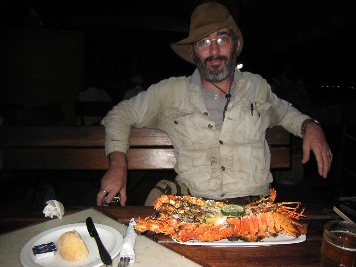 Roughing it abroad. Vincent Pardieu enjoys a small lobster in Pemba. Photo: Richard Hughes/Lotus Gemology