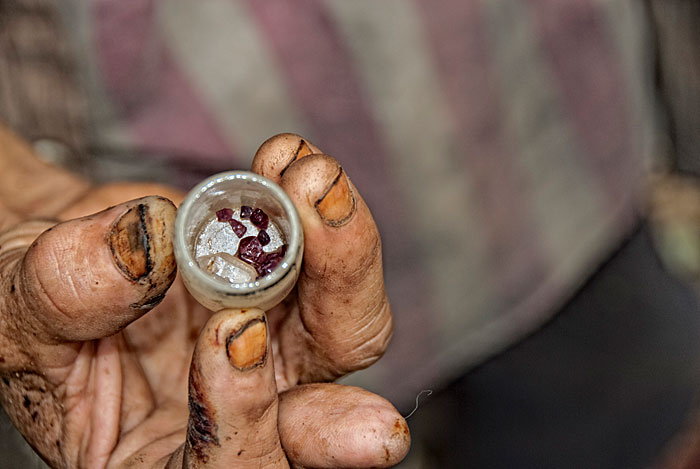 A handul of rubies, along with a piece of quartz from Thailand's last ruby miners. Photo © Richard W. Hughes, April 2009.