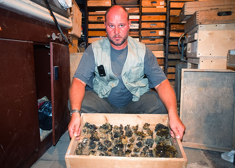 Nickolai Kouznetsov of Stoneflower Co., holding a large box of rutile specimens from the Caucasus Mountains in his Moscow office. Lotus Gemology.