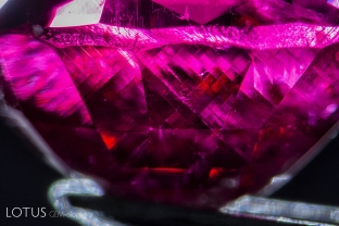 """After this ruby grew, it was exposed to high pressure, causing certain planes of atoms to glide into a twinned position. This secondary """"polysynthetic"""" twinning takes place along the rhombohedron faces and is common in many corundums. Twin planes cross at 86.1 and 93.9° angles."""