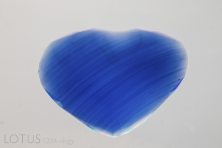 Curved color banding in a Verneuil-grown synthetic sapphire.