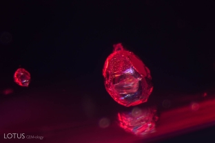 Two solid crystals of unknown identity perch inside this red spinel from Myanmar's Mogok Stone Tract.